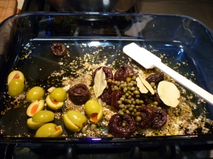 "Into a 9x13"" baking dish, mix together: 2 Tbsp. dried oregano; Salt and pepper; ¼ cup red-wine vinegar; ¼ cup olive oil; Handful pitted prunes; Handful green olives (mine were jumbo-sized, so I cut them in half); 2 Tbsp. capers with a little juice; 3 bay leaves"