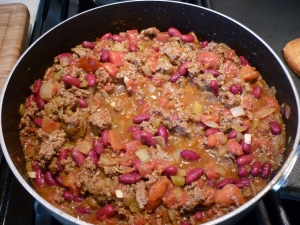 Fry ground beef, onion, and garlic together in oven-proof skillet. Stir in tomatoes, chiles, beans, and taco seasoning. Let simmer for a few minutes.