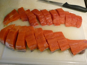 """Work with salmon fillets. Cut the fillets across into strips about 1"""" wide."""
