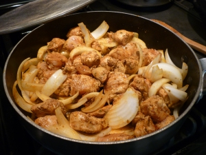 Meanwhile, heat 2 tablespoons olive oil in a separate large skillet over medium heat. Stir in marinated chicken and 1 Spanish onion; cook 5 minutes.