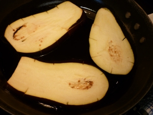 Pat eggplant slices with paper towel to remove moisture and fry slices in olive oil until mostly cooked through.