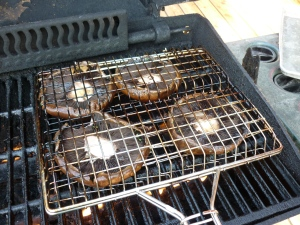 Rachael Ray recommends putting the mushroom caps on the grill and then placing a frying pan on top of them to gently press down. It works surprisingly well and I have done it that way many times. Grill for 3-4 minutes each side. This particular time that I'm showing you, I put the mushroom caps into a grill basket and grilled them that way. It worked great, too. You decide.
